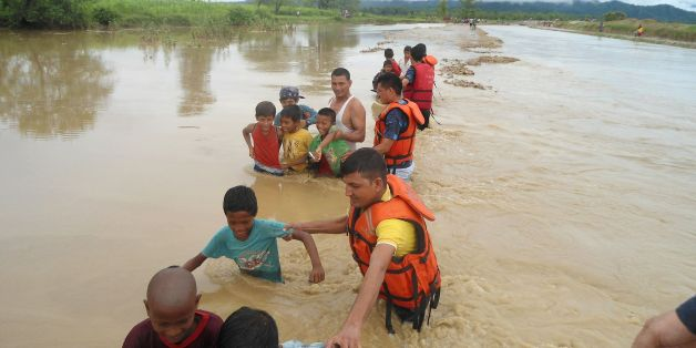 In this photograph taken on June 26, 2016, Nepalese Police personnel guide children through floodwaters at Babai Muinicipality-7 in Bardiya, some 400 kms southwest of Kathmandu. At least 33 people have died in floods and landslides triggered by heavy rains in Nepal and dozens more are missing, a government official said July 27. / AFP / Kamal Panthi        (Photo credit should read KAMAL PANTHI/AFP/Getty Images)