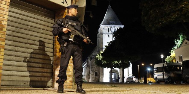 French riot police guards the street to access the church where an hostage taking left a priest dead in Saint-Etienne-du-Rouvray, Normandy, France, Tuesday, July 26, 2016. Two attackers invaded a church Tuesday during morning Mass near the Normandy city of Rouen, killing an 84-year-old priest by slitting his throat and taking hostages before being shot and killed by police, French officials said. (AP Photo/Francois Mori)