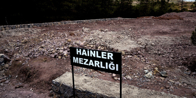 """CORRECTS PHOTOGRAPHER'S NAME - A sign reading in Turkish """"Traitors' Cemetery"""" is seen in front of unmarked graves, built specifically to hold the bodies of coup plotters who died in the failed military coup of July 15, in eastern Istanbul Wednesday, July 27, 2016. In the week following the attempted coup, the local municipality announced it intended to set up a cemetery specifically for those involved - traitors who didn't deserve a decent burial. (AP Photo/Bram Janssen)"""