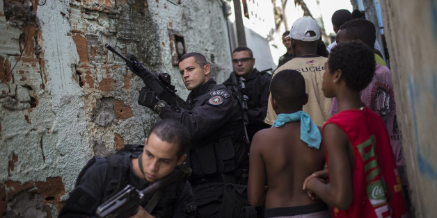 "Special Operations Battalion (BOPE) Police officers patrol as residents move about the Sao Carlos slum complex where the bodies of two men were found in Rio de Janeiro, Brazil, Friday, May 15, 2015. The bodies of two young men were discovered late Thursday in this so-called ""pacified"" slum where police are present. (AP Photo/Felipe Dana)"