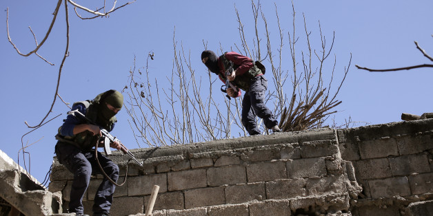 Militants from the Kurdistan Workers' Party, or PKK, run as they attack Turkish security forces in Nusaydin, Turkey, Tuesday, March 1, 2016. Turkish authorities say a curfew in the district of Cizre in the southeastern province of Sirnak will be lifted at 5 a.m. on Wednesday. The curfew was declared on Dec. 14, coupled with large-scale military operations to flush out Kurdish militants who set up ditches and trenches to keep security forces at bay.(AP Photo/Cagdas Erdogan)