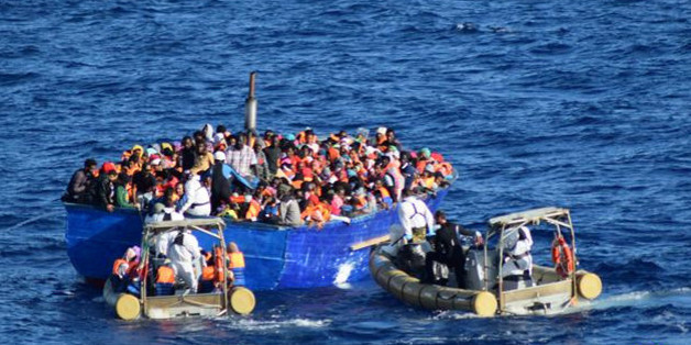 Migrants sit in their boat during a rescue operation by Italian navy ship Borsini (unseen) off the coast of Sicily, Italy, in this handout picture courtesy of the Italian Marina Militare released on July 19, 2016.  Marina Militare/Handout via REUTERS    ATTENTION EDITORS - THIS PICTURE WAS PROVIDED BY A THIRD PARTY. FOR EDITORIAL USE ONLY.