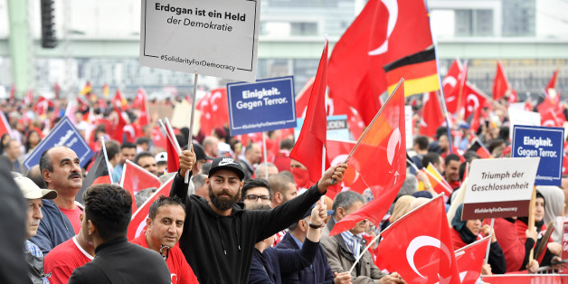 A Turkish protestor holds a banner reading 'Erdogan is a hero of democracy', left,  during a demonstration in Cologne, Germany, Sunday, July 31, 2016. Supporters of Turkish President Recep Tayyip Erdogan  demonstrate in Cologne amid heavy police presence. Some 30,000 participants are expected at Sunday's demonstration, which comes amid tensions following the failed coup attempt in Turkey and concern in Germany over the extent of the Turkish government's subsequent crackdown. (AP Photo/Martin Meissner)