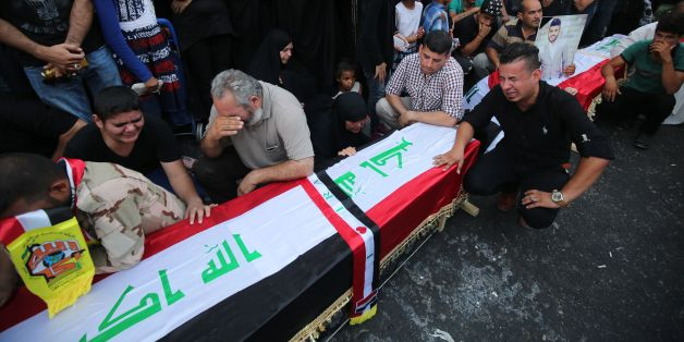 Iraqis mourn next to empty coffins at the site of the explosion in Baghdad's Karrada shopping district during a symbolic funeral on July 10, 2016 for the victims of the attack.In what was one of the deadliest attacks ever to hit Iraq, a suicide bomber blew up a minibus packed with explosives in a Baghdad shopping district teeming with people ahead of the Eid al-Fitr holiday, sparking widespread anger against the government. / AFP / AHMAD AL-RUBAYE        (Photo credit should read AHMAD AL-RUBAYE