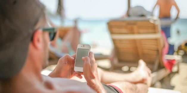 Man using smart phone at sea
