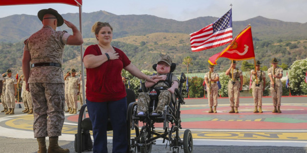 Wyatt Gillette, 8, front right, visits Camp Pendleton, Calif., Saturday, July 30, 2016, with his mother Felicia, front center, as his father, Marine Staff Sgt. Jeremiah Gillette salutes during a ceremony where the young Gillette received an award to become an honorary Marine. Gillette, who had the genetic disease  Aicardi-Goutieres syndrome, which causes seizures and kidney failure, died Sunday, July 31, 2016. (Lance Cpl. Angelica Annastas/U.S. Marine Corps via AP)