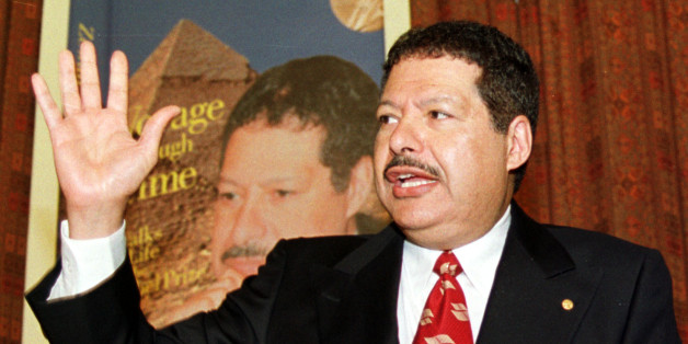 """Egyptian-American Nobel chemistry laureate Ahmed Zewail gestures to reporters in Cairo, Feb. 4, 2002. In a new autobiography called """"Voyage Through Time...Walks of Life to the Nobel Prize,"""" Zewail narrates his journey from a small village on the west bank of the Nile Delta to the California Institute of Technology. He teaches physics and chemistry there now and directs the Laboratory for Molecular Sciences. (AP Photo/Mahmoud Nour Eddin)"""