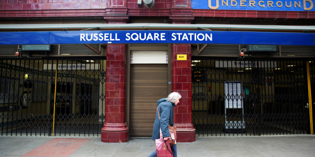 FILE PHOTO - A woman walks past a closed entrance of Russell Square underground station in London April 29, 2014.   REUTERS/Neil Hall/File Photo