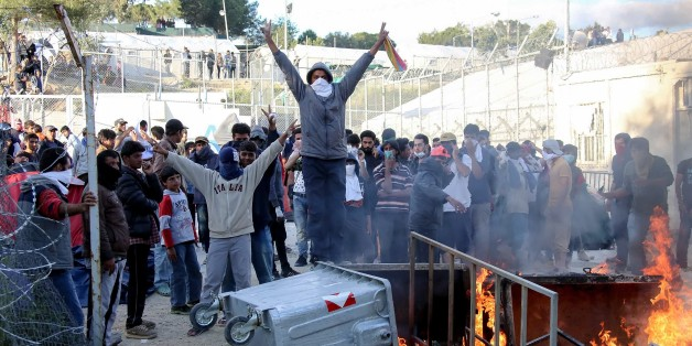 Migrants make a victory sign as garbage bins burn at the Moria migrant detention center on the northeastern Greek island of Lesbos, Tuesday, April 26, 2016. A protest broke out in Moria during a visit there by the Greek migration affairs minister and a Dutch official, with protesters, mainly unaccompanied teenagers, setting fires and riot police on standby. (Petros Tsakmakis/InTime News via APos
