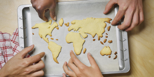 Hands reaching for world map cookies