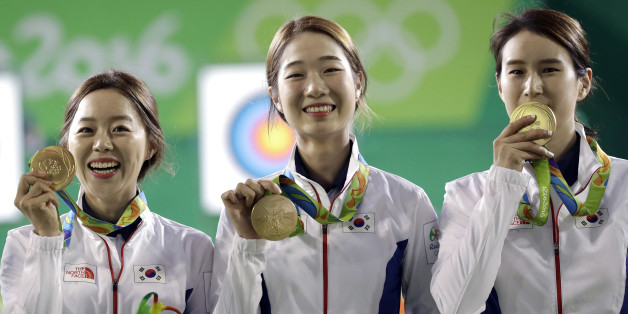 From left, South Korea's Chang Hye-jin, Choi Mi-sun and Ki Bo-bae shows their gold medals to photographers during the awards ceremony of the women's team archery competition at the Sambadrome venue during the 2016 Summer Olympics in Rio de Janeiro, Brazil, Sunday, Aug. 7, 2016. (AP Photo/Alessandra Tarantino)