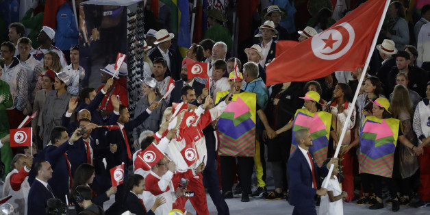 Oussama Mellouli carries the flag of Tunisia during the opening ceremony for the 2016 Summer Olympics in Rio de Janeiro, Brazil, Friday, Aug. 5, 2016. (AP Photo/Markus Schreiber)