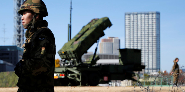 FILE PHOTO - Members of the Japan Self-Defence Forces stand guard near Patriot Advanced Capability-3 (PAC-3) land-to-air missiles, deployed at the Defense Ministry in Tokyo December 7, 2012.  REUTERS/Issei Kato/File Photo