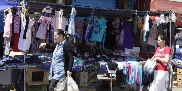 Women walks past a clothing stall during the holy month of Ramadan in the old city of Tunis August 10, 2012. REUTERS/Zoubeir Souissi (TUNISIA - Tags: RELIGION SOCIETY)
