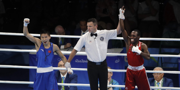 The referee looks at China's Bin LV, left, as he lifts the hand of Kenya's Peter Mungai Warui after a men's light flyweight 49-kg preliminary boxing match at the 2016 Summer Olympics in Rio de Janeiro, Brazil, Monday, Aug. 8, 2016. (AP Photo/Jae C. Hong)