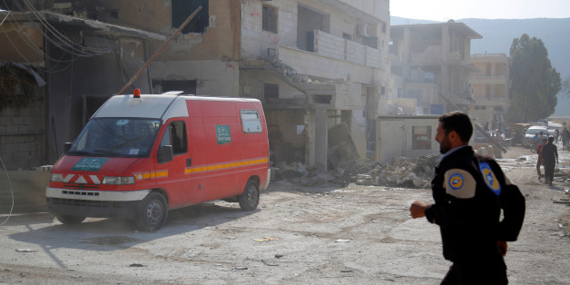 A civil defence member runs near an ambulance after an airstrike on a hospital in the town of Meles, western Idlib city in rebel-held Idlib province, Syria August 6, 2016. REUTERS/Ammar Abdullah