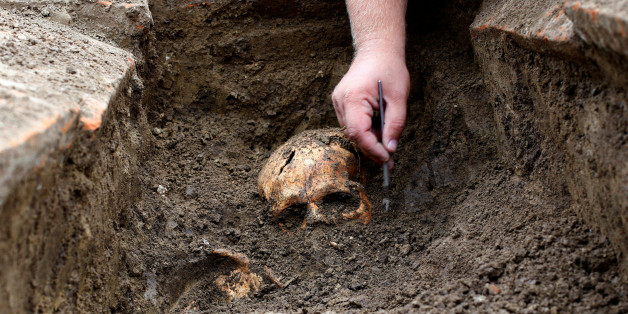 An archaeologist works over an uncovered skeleton at the Viminacium site, around 100km east from Belgrade, Serbia August 8, 2016. Picture taken August 8, 2016. REUTERS/Djordje Kojadinovic