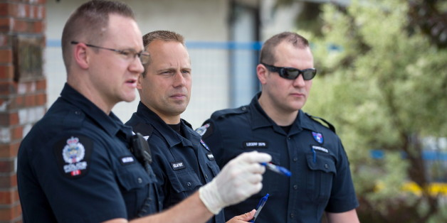 Investigators inspect the scene where a police officer was shot and killed on Monday, in Edmonton, June 9, 2015. Constable Daniel Woodall was killed and another officer Sergeant Jason Harley injured on Monday in Edmonton, Canada, after an exchange of fire with Norman Raddatz, police said. The officers were attempting to arrest Raddatz on Monday evening, when the shootings happened, police said. REUTERS/Topher Seguin