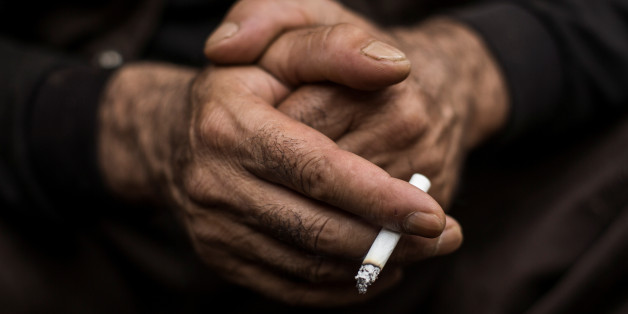 A Kurdish worker smokes a cigarette as he takes a break at a demolition site in Chiba east of Tokyo, October 21, 2015.  To match Special Report JAPAN-KURDS/  REUTERS/Thomas Peter