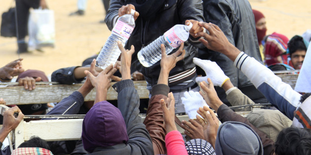 Evacuees receive bottles of water during food distribution at the UNHCR refugee camp near the border crossing of Ras Jdir, after fleeing the violence in Libya March 9, 2011. REUTERS/Pascal Rossignol (TUNISIA - Tags: CIVIL UNREST POLITICS SOCIETY)