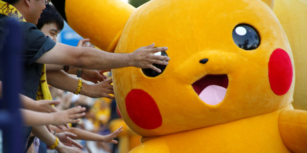 People touch a performer wearing Pokemon's character Pikachu costume during a parade in Yokohama, Japan, August 7, 2016. REUTERS/Kim Kyung-Hoon