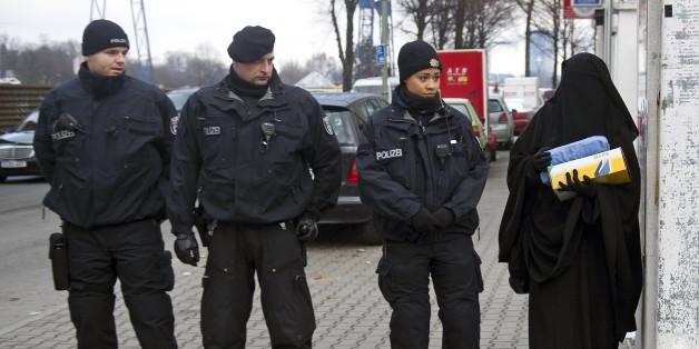 Ein Frau mit Burka begegnet vor einem Salafisten-Treffen deutschen Polizisten