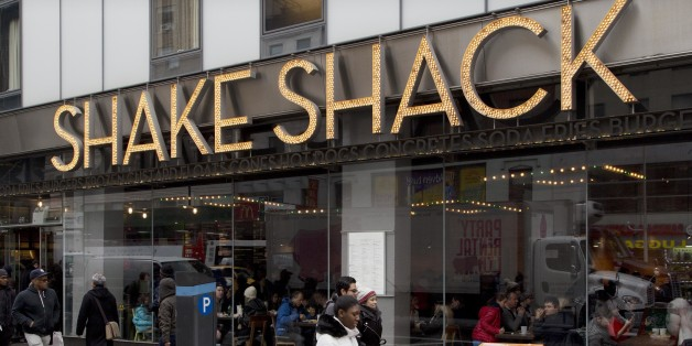 FILE - In this Friday, March 4, 2016, file photo, people walk past a Shake Shack in New York. Shake Shack reports financial results Thursday, May 12, 2016. (AP Photo/Mark Lennihan, File)