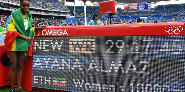 Ethiopia's Almaz Ayana celebrates next to a board displaying her new world record after the Women's 10,000m during the athletics event at the Rio 2016 Olympic Games at the Olympic Stadium in Rio de Janeiro on August 12, 2016.   / AFP / FRANCK FIFE        (Photo credit should read FRANCK FIFE/AFP/Getty Images)