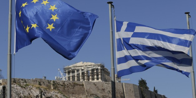 The Greek, right, and the European flags wave under the ancient Acropolis hill in Athens, Sunday, July 5, 2015. Greeks lined up at polling stations and ATMs alike Sunday as the country voted on its financial future, choosing in a referendum whether to accept creditors' demands for more austerity in return for rescue loans or defiantly reject the deal.  (AP Photo/Petr David Josek)