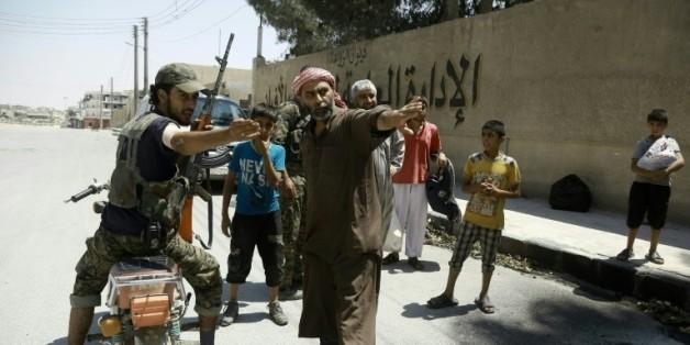 Un membre des Forces démocratiques syriennes (FDS) indique le chemin aux civils fuyant un quartier contrôlé par les jihadistes de l'EI à Minbej, le 7 août 2016