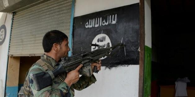 Un soldat de l'armée afghane pointe son arme sur un drapeau de Daech, le 26 juillet 2016 © AFP/Archives NOORULLAH SHIRZADA