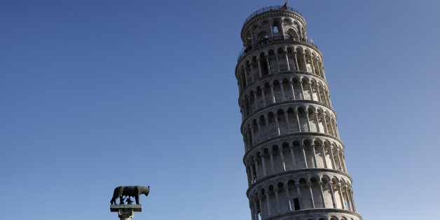 A small sculpture of 'Romulus and Remus' is seen in front of the Leaning Tower of Pisa July 19, 2012. The 'Torre di Pisa' is the bell tower of the Cathedral of the Italian city of Pisa, known worldwide for its unintended tilt to one side. The tower began to lean in 1178 due to soft ground which could not properly support the structure's weight. REUTERS/Clarissa Cavalheiro (ITALY - Tags: SOCIETY TRAVEL)