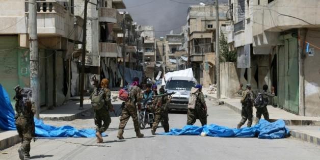Des membres de forces démocratiques syriennes dans une rue de Minbej en Syrie, le 7 août 2016