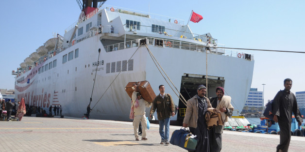 Egyptian workers who fled the unrest in Libya and were stranded in Tunisia, carry their baggage upon their arrival aboard a Tunisian ship in the Mediterranean port city of Alexandria, Egypt Friday, March 4, 2011. (AP Photo/Tarek Fawzy)