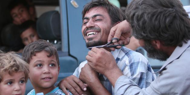 Ein Mann schneidet den Bart einer ehemaligen Geisel des IS in Manbidsch