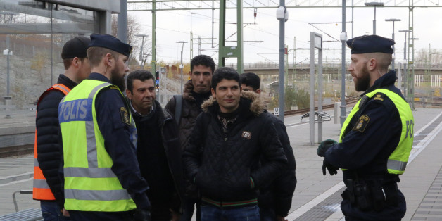 Swedish police officers speak to a group of people at the Hyllie train station near Malmo, Sweden, November 12, 2015. Swedish police began bordering trains on Thursday arriving from Denmark as they imposed the first large-scale border controls in two decades to deal with a refugee influx, but there were no signs the numbers of immigrants were slowing. REUTERS/Staff
