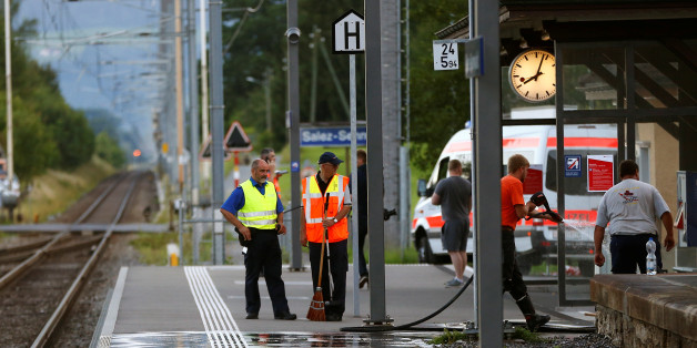 A Swiss police officer stands near workers cleaning a platform after a 27-year-old Swiss man's attack on a Swiss train at the railway station in the town of Salez, Switzerland August 13, 2016. REUTERS/Arnd Wiegmann        TPX IMAGES OF THE DAY