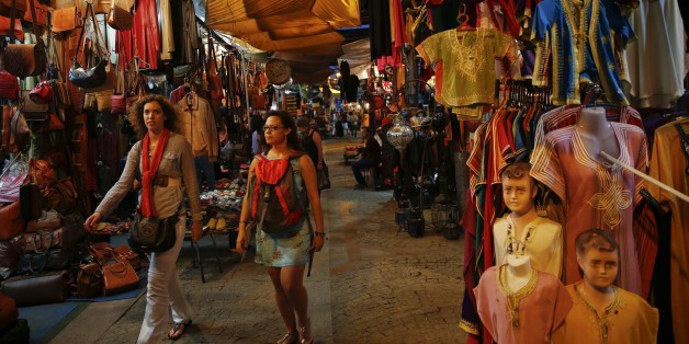 "Tourists stroll between shops in Rue des Consuls in Rabat's Medina September 25, 2014. UNESCO made Rabat a World Heritage Site two years ago and media and tour operators call it a ""must-see destination."" But it seems the tourist hordes have yet to find out. While visitors are getting squeezed through the better-known sites of Marrakesh and Fez, the old part of Rabat - with its beautiful Medina and Kasbah of the Udayas - remains an almost unspoiled oasis of calm. Smaller and more compact, its lab"