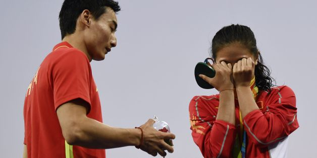 TOPSHOT - Silver medallist China's He Zi (R), reacts she receives a marriage proposal from Chinese diver Qin Kai during the podium ceremony of the Women's diving 3m Springboard Final at the Rio 2016 Olympic Games at the Maria Lenk Aquatics Stadium in Rio de Janeiro on August 14, 2016.   / AFP / CHRISTOPHE SIMON        (Photo credit should read CHRISTOPHE SIMON/AFP/Getty Images)