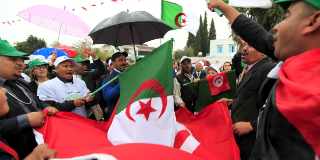 People holding Algerian flags and Tunisian flags march down a boulevard near the Bardo museum, during a ceremonial reopening of the museum in Tunis March 24, 2015. The museum held a ceremonial reopening on Tuesday a week after gunmen claiming alliance with Islamic State killed 20 foreign tourists in an attack aimed at wrecking the country's vital tourism industry. Several thousand Tunisians and foreign visitors to an international forum also marched in the capital Tunis to show solidarity with the Bardo victims who included Japanese, Spanish, Italians and Colombians. REUTERS/Anis Mili