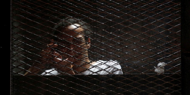 "Egyptian photojournalist Mahmoud Abu Zeid, also known as ""Shawkan"", gestures behind bars in his trial at on the outskirts of Cairo, Egypt May 31, 2016. REUTERS/Amr Abdallah Dalsh"