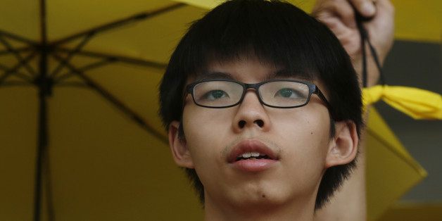 Student leader Joshua Wong, attends a protest outside a court in Hong Kong, Friday, July 17, 2015. Wong along with other three pro-democracy protesters appeared in court on Friday after being charged with obstructing police officers as they took part in an anti-China protest outside the Liaison Office in June, 2014.(AP Photo/Kin Cheung)