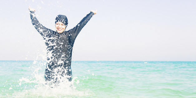 young woman in burkini splashing water, persian gulf, jumeirah beach in dubai