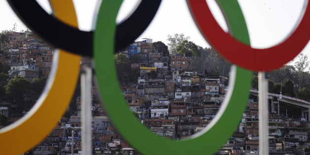 Houses from a favela are photographed through the Olympic rings prior to the opening ceremony for the 2016 Summer Olympics in Rio de Janeiro, Brazil, Friday, Aug. 5, 2016. (AP Photo/Jae C. Hong)