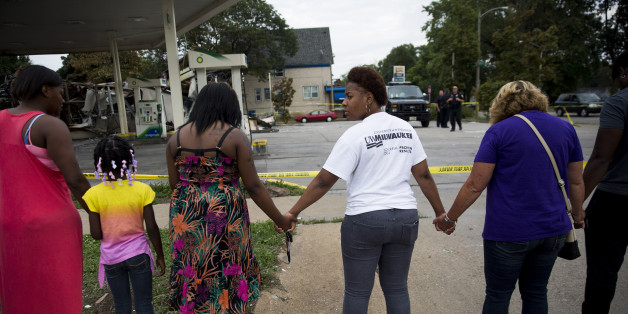 Jasmine Newson, 21, turns around while praying at a gas station that was destroyed by rioters after a fatal police shooting two days prior, on Monday, Aug. 15, 2016, in Milwaukee, Wis. (Armando L. Sanchez/Chicago Tribune/TNS via Getty Images)