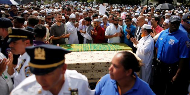 Des hommes prient autour des cercueils contenant les corps d'un imam et de son assistant tués par balles, à New York le 15 août 2016