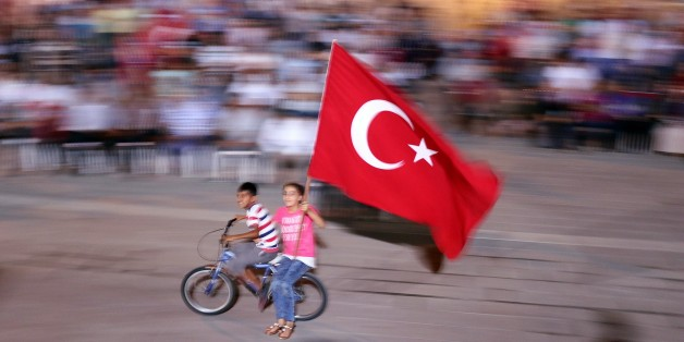 HATAY, TURKEY - JULY 30: Two Children wave Turkish flag as they ride on bicycle as people gather to protest against July 15 failed military coup attempt, at Iskenderun district of Hatay, Turkey on July 30, 2016. Turkish officials accuse U.S.-based Turkish citizen Fetullah Gulen plotting to overthrow the government of President Erdogan as the culmination of a long running campaign to infiltrate Turkish institutions including the military, the police and the judiciary. (Photo by Burak Milli/Anadolu Agency/Getty Images)