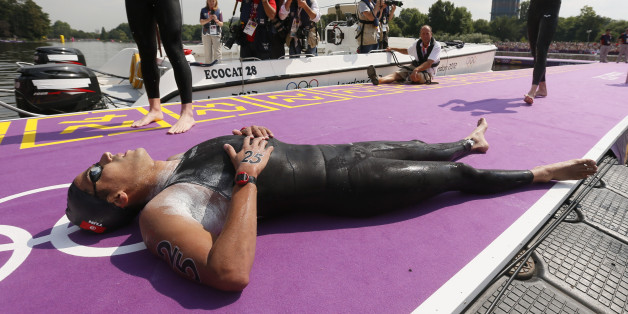 Tunisia's Oussama Mellouli relaxes after winning gold in the men's 10km marathon swimming at Hyde Park during the London Olympic Games August 10, 2012.           REUTERS/Stefan Wermuth (BRITAIN  - Tags: OLYMPICS SPORT SWIMMING)