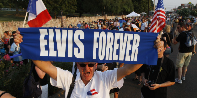 Elvis Presley fan Orlando Bruno of Paris, France holds up his sign as he waits in line to visit Presley's gravesite on the eve of the 30th anniversary of Presley's death, 15 August 2007 at Graceland, Presley's home in Memphis, Tennessee. Fans are gathering to mark the 30th anniversary of the entertainers death on 16 August. AFP PHOTO/Stan HONDA (Photo credit should read STAN HONDA/AFP/Getty Images)