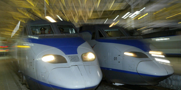 A South Korean KTX train (L) prepares to depart for Pusan city at the Seoul railway station April 1, 2004. South Korea's first high-speed railway service began before dawn on Thursday when a sleek, French-designed bullet train slipped out of Seoul bound for the southern port city of Pusan, now less than three hours away. REUTERS/Kim Kyung-Hoon  KKH/GB